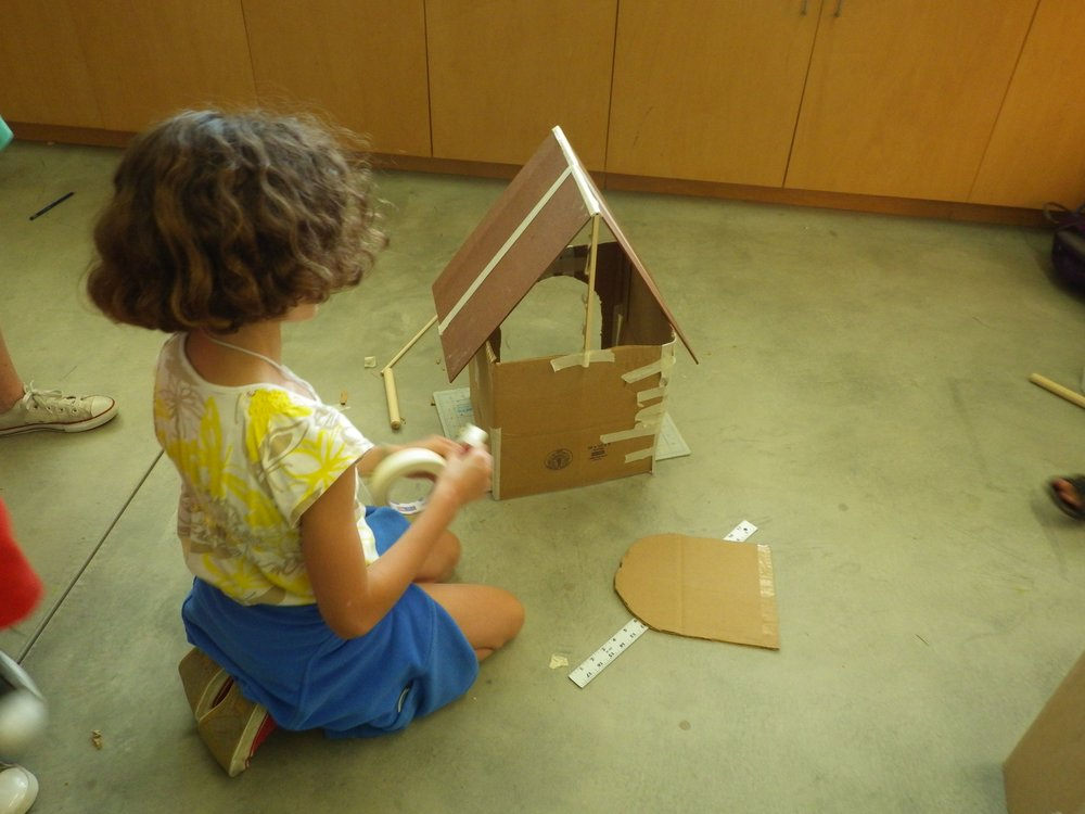 A young maker prototypes a dog house before beginning to build