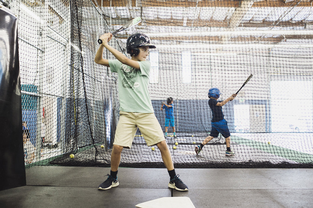 young sirious students taking their  swings in the sirious cages.