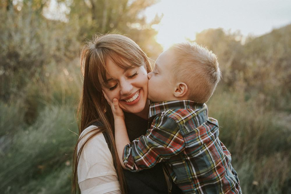 A tender moment between a mother and son, with the young boy kissing his mother cheeks, photographed by the premier Boise Idaho family photographer, Lauren Guiffre