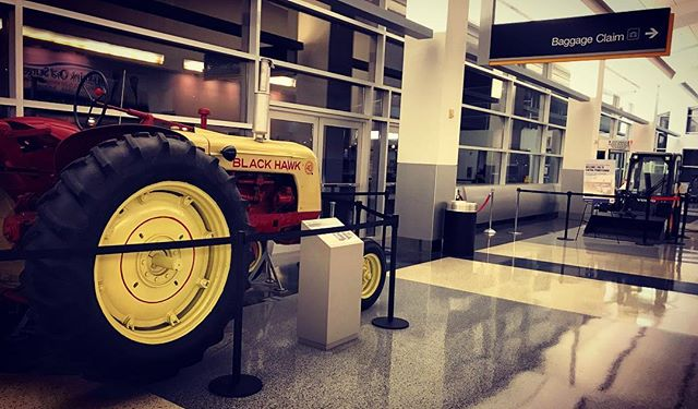 I'm near my parents' house.  I know this simply because there's farm equipment on display in baggage claim.