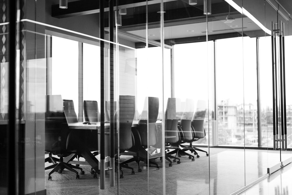 A long grey boardroom office table. Photo by  Drew Beamer  on  Unsplash