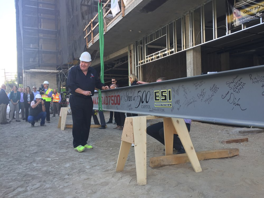 Developer Brian Obie signs the final beam before it is hoisted into place