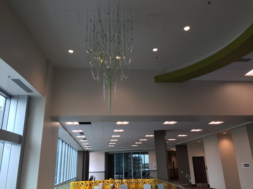 Green-toned chandaliers appear throughout the building