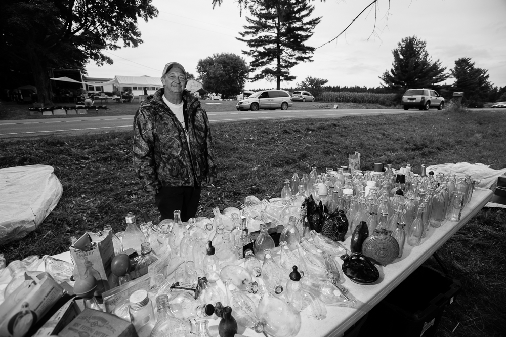 """Randy Weaver, whom rents property in Union Springs sells his collection of various glass vessels – including antique nursing bottles during the annual """"50 Mile Yardsale"""", Saturday, July 20, 2016 along Route 90 in the Cayuga Lake region of the Finger Lakes, New York. Mr. Weaver acquires most of his collectibles from the internet."""