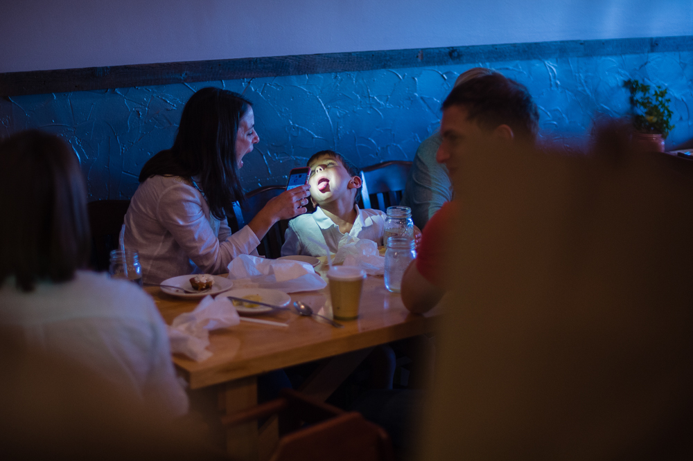 A patron check her son's rapidly growing teeth after enjoying their family meal.