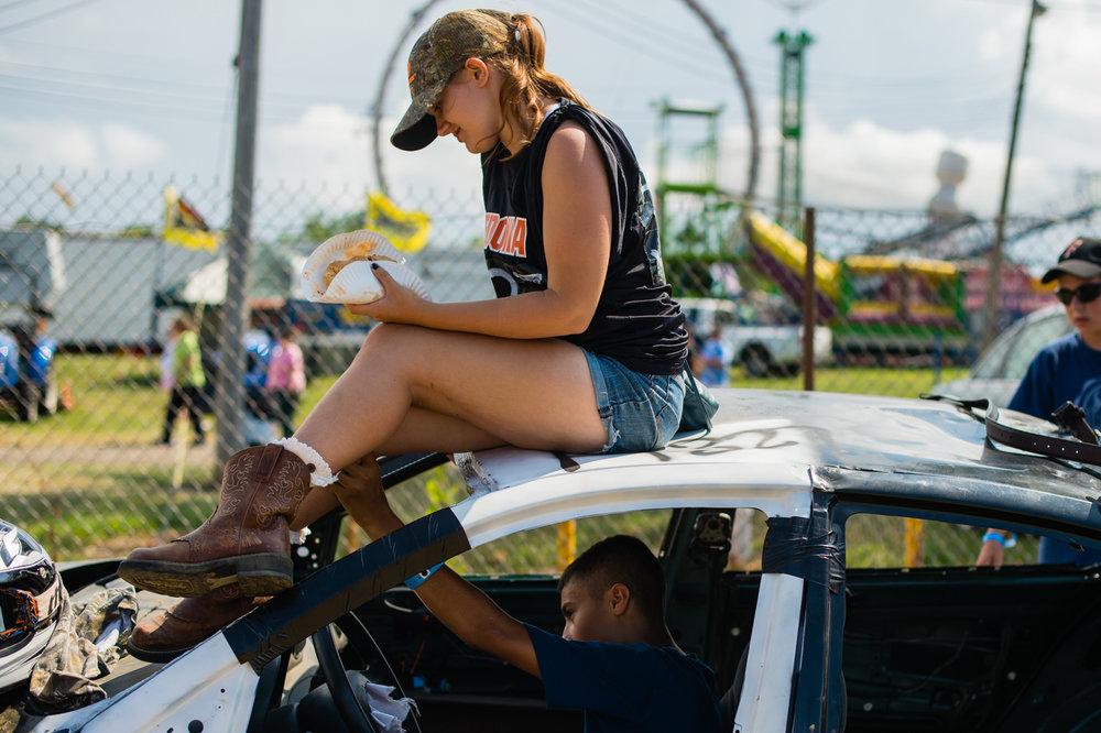 Brooke Erik, 17, hangs out on top of her cousin's demolition derby car in Dunkirk, NY, while family friend Jay Cevic flirts with her.