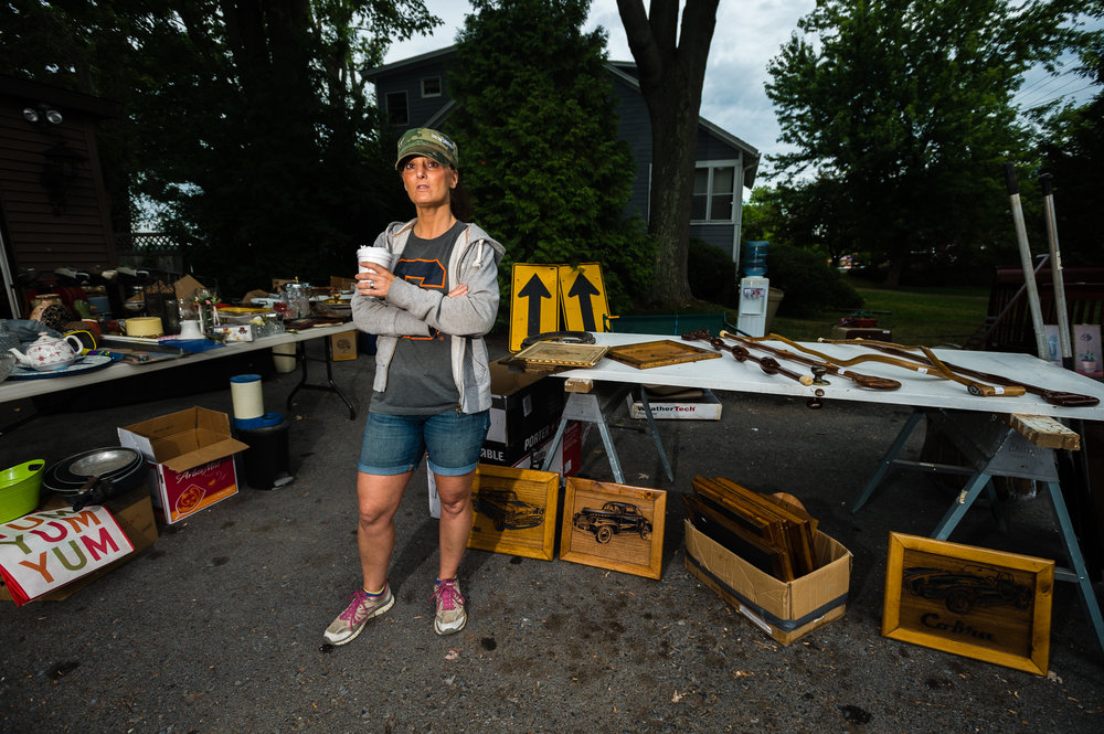 """Village of Cayuga resident Alicia Maywalt helps oversee a neighbor's collection of goods for sale during the annual """"50 Mile Yardsale"""", Saturday, July 30, 2016 along Route 90 in the Cayuga Lake region of the Finger Lakes, New York."""