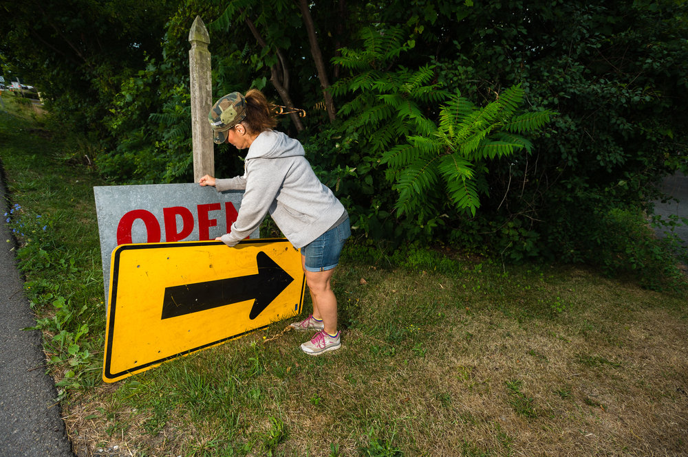 """Village of Cayuga resident Alicia Maywalt, whom was helping to oversee a neighbor's collection of goods for sale during the annual """"50 Mile Yard Sale"""" sets out an old highway sign to help draw attention to the property, Saturday, July 30, 2016 along Route 90 in the Cayuga Lake region of the Finger Lakes, New York."""