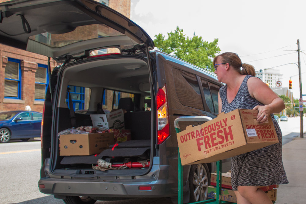 412 Food Rescue volunteer Rebecca Maclean loads her car with donations from whole foods that she will take to Lawrenceville United, who distribute the food to refugee families in the area.