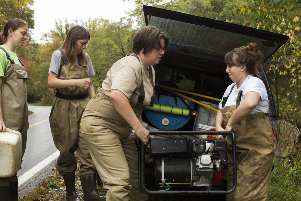 Emily Keil-Loudner, left to right, and Amy Mackey watch Abby Costilow and Brooke Stokes unload a generator used for electrofishing in Sandy Run Creek in McArthur, Ohio, on October 9, 2017.