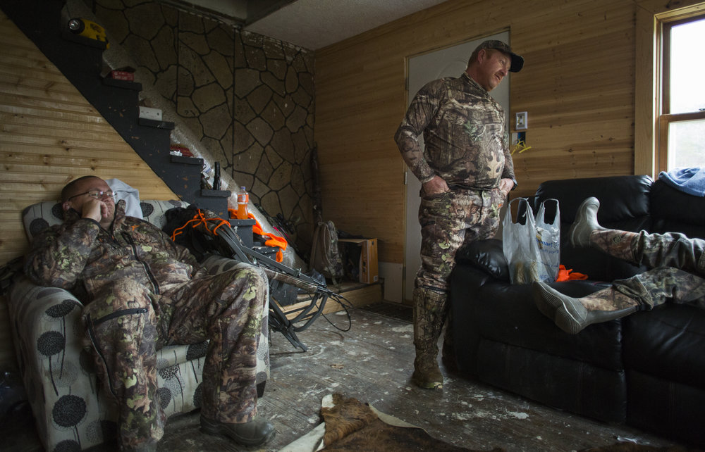 Tom Denney, left to right, Dennis Pendarvis, and Tristen Denney relax back at camp after an unsuccesful morning of hunting in Wellston, Ohio, on November 19, 2017.