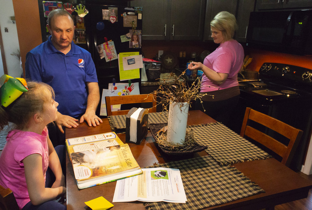 "Chaz and Allison, right, Richards help their daughter Braylee, left, with her homework while cooking dinner. Allison and Chaz both work in Athens, but choose to stay in Glouster because of the good people there, and the low cost of living. ""If you stay out of the wrong crowd it's easy living here,"" said Chaz Richards."