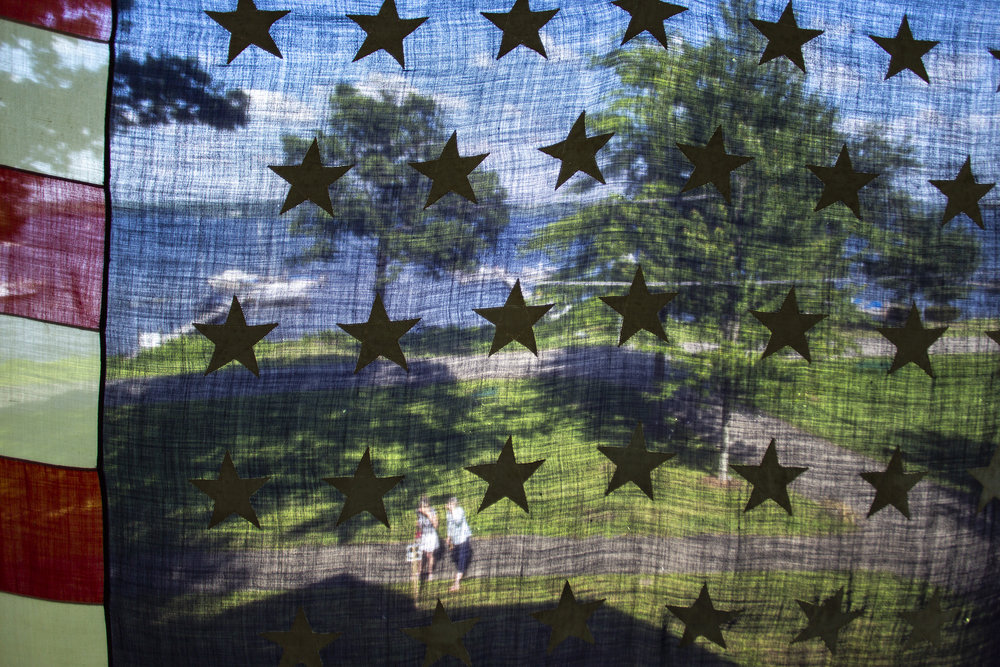 Passersby read a plaque about the 46 star American flag, Sunday, July 1, 2018, at the Karslake family Cottage on S. Lake Drive in Chautauqua, NY. The Karslakes say this flag was found when they purchased the home in 1950 and they proudly display it every year for Independence Day. The American flag officially had 46 stars between 1908 and 1912, though no one has found an exact date for the flag.