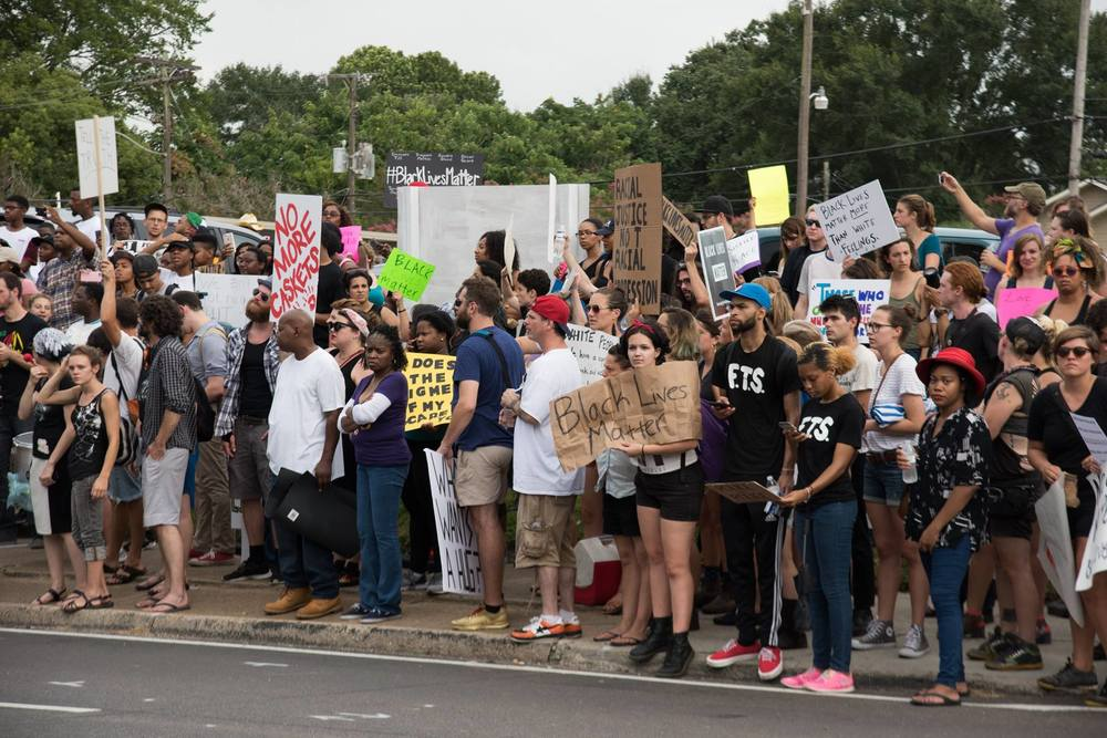 Protestors march on sidewalks down Government Street. Photo courtesy of George Castillo.