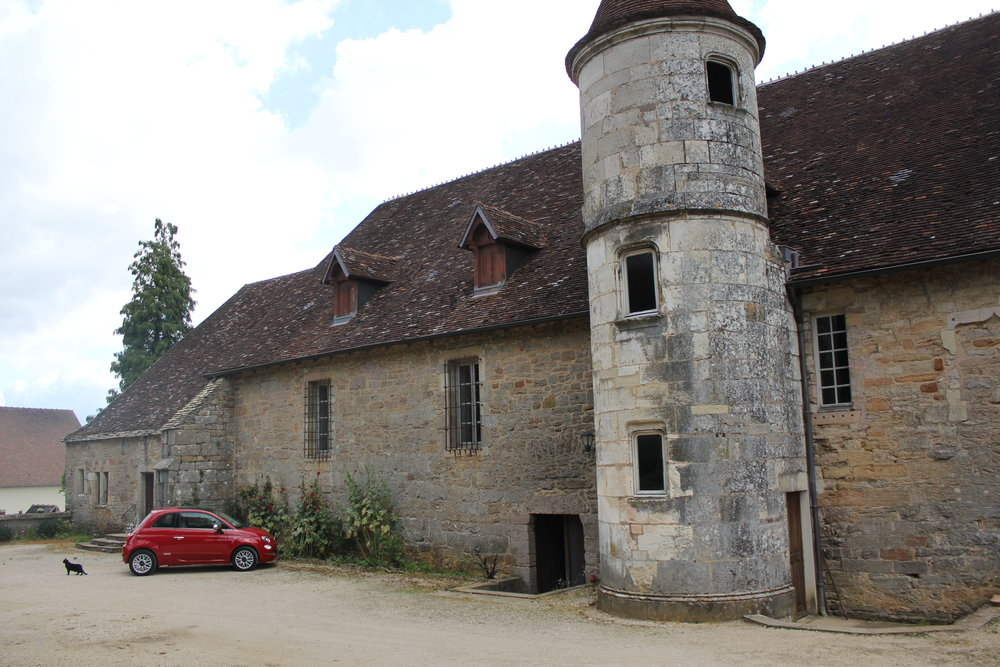 Our little red Fiat rental car outside Domaine Joilet; The Chateau cat looks on.