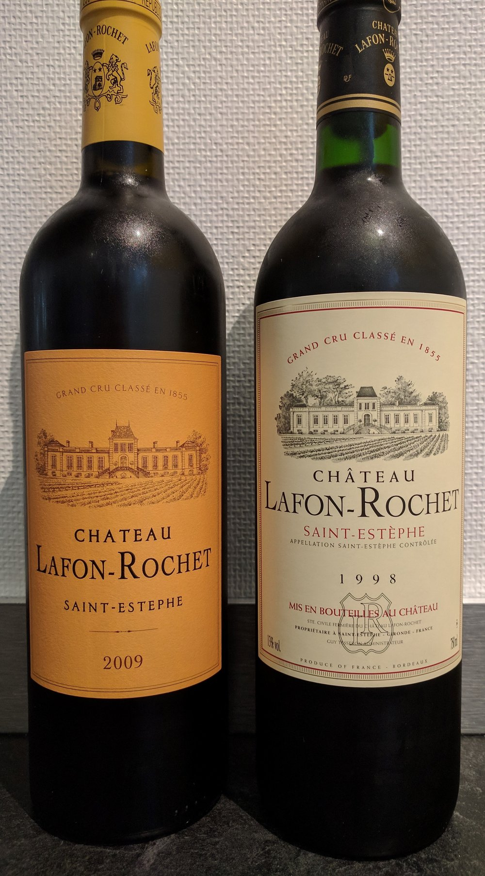 -                 Chateau Lafon-Rochet implemented the yellow label to match its repainted estate. A label from before the estate's repainting is on the right.