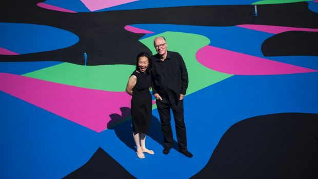 Above:  Architect and arts patron Corbett Lyon with his wife Yueji standing on Reko Rennie's  Visible Invisible , painted on the base of his second Housemuseum of contemporary art in Kew. Photo: Josh Robenstone
