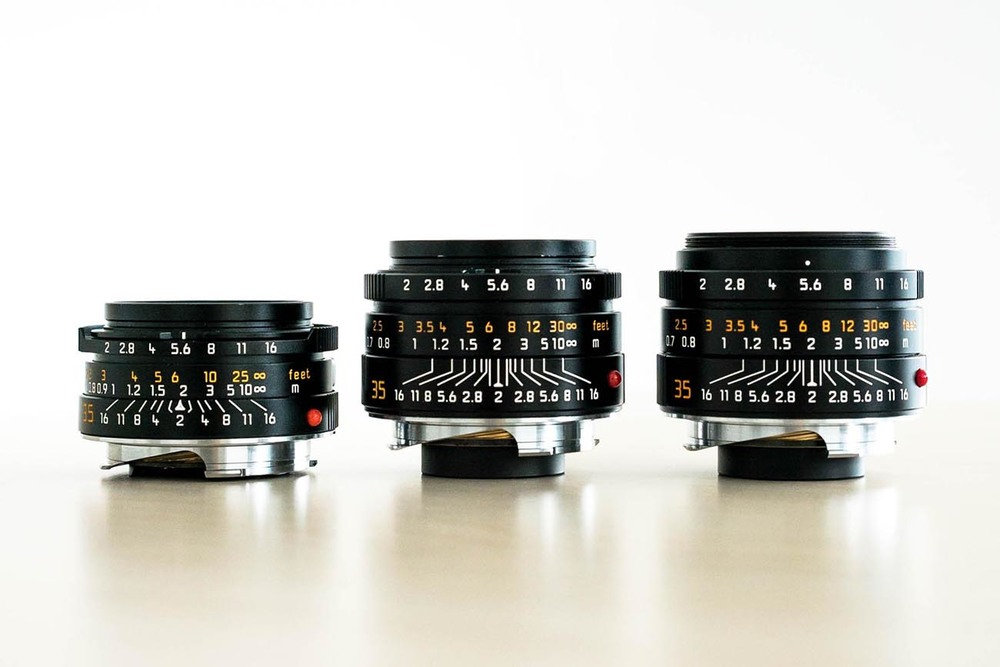 "Three generations of 35mm Summicrons. From Left to Right - pre-aspherical 35mm Summicron version IV ""King of Bokeh"", 35mm Summicron ASPH (previous version), and 35mm Summicron ASPH version 2 (current version). Also notice the white scuff marks on the previous version Summicron (in the middle). That's where the paint was scratched off by the clips of the rubber hood."