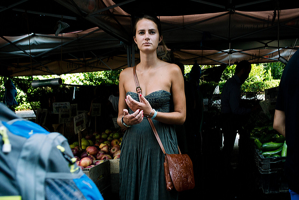 The title image of this post was shot blindly with less than a split second. The subject was looking straight at me, just as I turned around to face her. It was for me a perfect image in my head. She was just coming into the light, wearing a green shoulderless maxi dress, with a produce stand, largely in shadow behind her - also very green. I just took the shot, and hoped for the best. In the end, the image was slightly out of focus, and very distorted, given the short focusing distance from the 28mm lens. I had to do a noticeable amount of vertical and horizontal transformation in Lightroom, in addition to a rotational correction. The focus was improved with the camera shake reduction filter in Photoshop. The image was exported large from Lightroom, and downsized in Photoshop. After all that work in post, this image became usable.