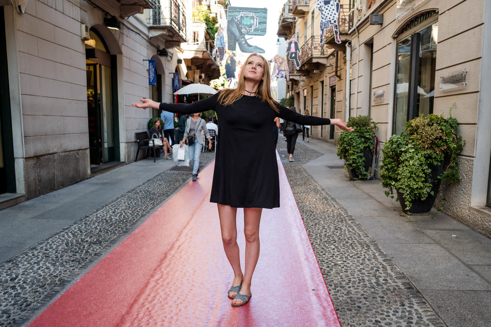 On some red carpet, on a narrow cobblestone lane, at the Brera district.