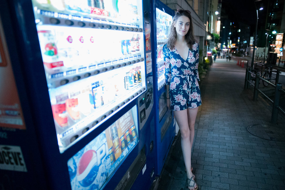 Leaning against a Japanese vending machine.