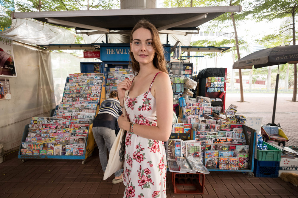 In front of a newsstand by Central Pier with the vender visible behind Anna.