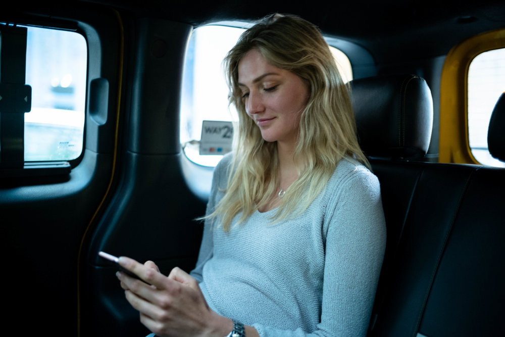 Lydia looking at her social media feed, in a Yellow Cab, on her way back to the hotel. Anna is seated up front, obscured by the bubble partition.