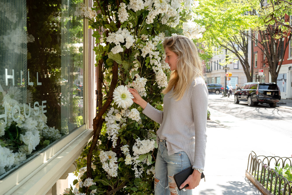 Lydia inspecting fake flower on Bleeker Street, in the West Village.