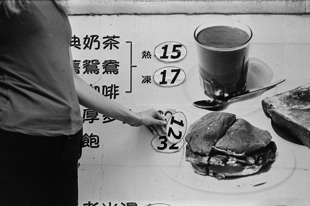 Kodak Tri-X 400 @ 28mm Focal Length - Interacting with the environment by looking under a peeling price sticker. Compositional variables include background signage.