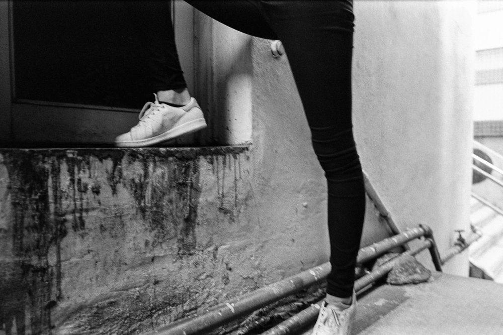 Kodak Tri-X 400 @ 28mm Focal Length - Interacting with the environment by stepping on an edge of a doorway. Compositional variables include wall texture, external plumbing, and stains.