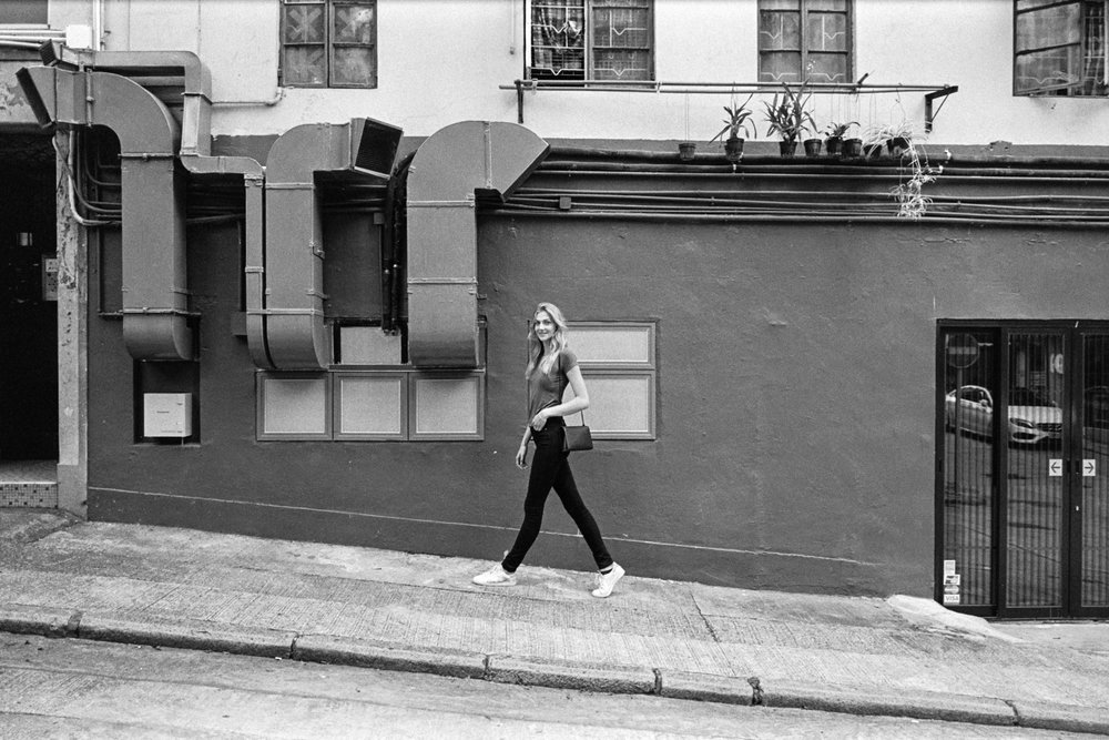 Kodak Tri-X 400 @ 28mm Focal Length - Walking uphill. Compositional variables include wall texture, HVAC vents, and windows.