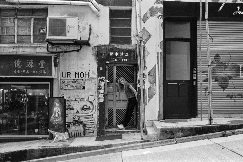 Kodak Tri-X 400 @ 28mm Focal Length - Interacting with the environment by leaning against a doorway. Compositional variables include rectilinear lines of doorways, buildings, and an incline on the road.
