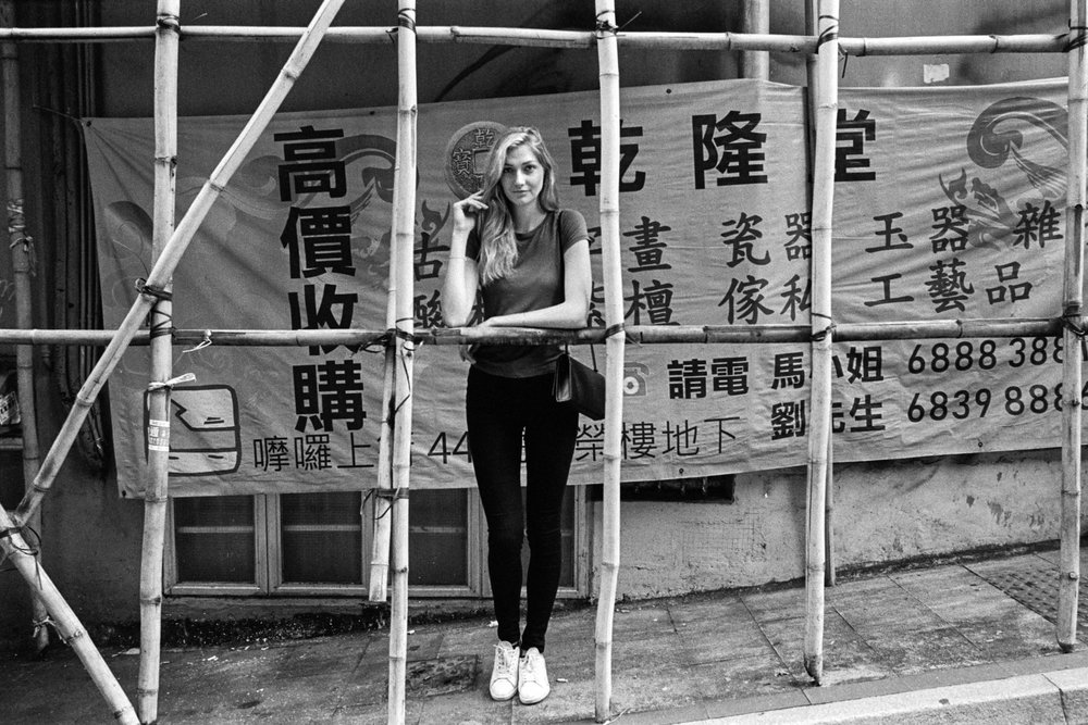 Kodak Tri-X 400 @ 28mm Focal Length - Interacting with the environment by leaning on bamboo scaffolding. Compositional variables include scaffolding, and background signage.