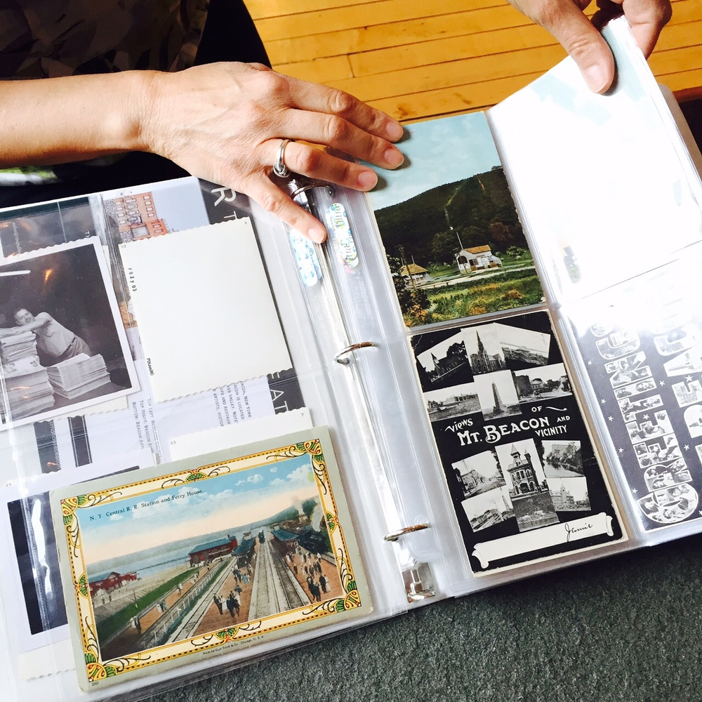 Diane Lapis, Trustee of the Beacon Historical Society, showing their collection of postcards, which serve as inspiration for a new column at A Little Beacon Blog.