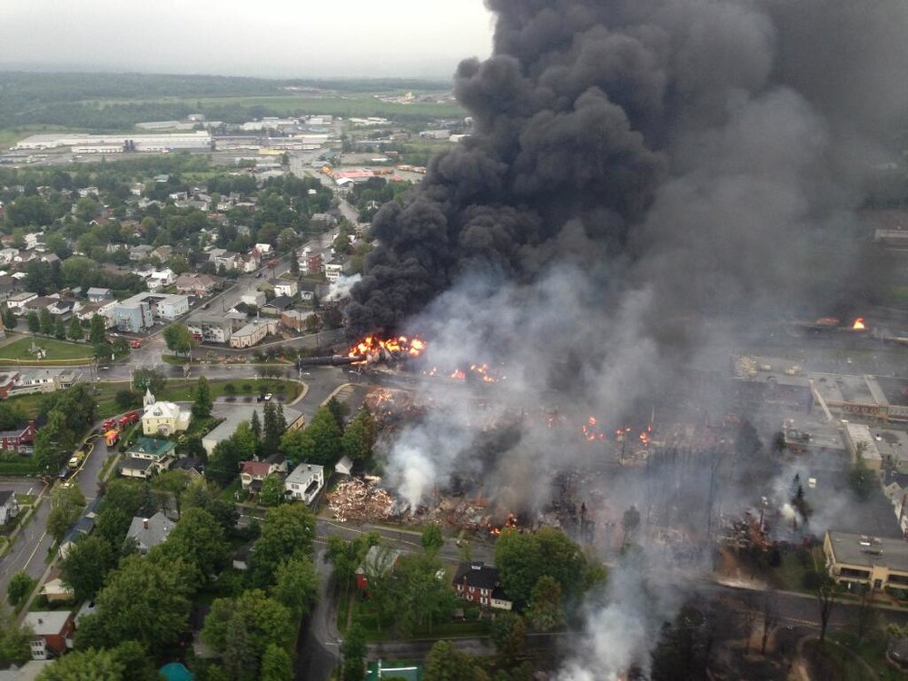 Lac-Mégantic, Quebec in 2013  while burning after a train carrying oil derailed and rolled down a mountain into the town, wiping out more than 30 buildings and killing 47 people. Photo credit: Photo from a police helicopter, published at  Wikipedia