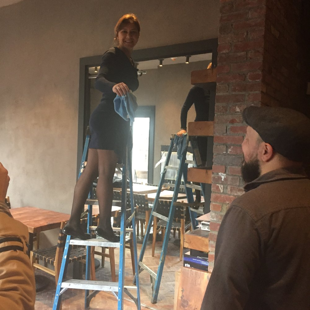This scene could be one from a musical about the makings of a restaurant, but it is co-owner Alla wiping shelves in preparation for a walk-through by people who were getting sneak peeks of the restaurant before it opened. Photo Credit: Katie Hellmuth Martin