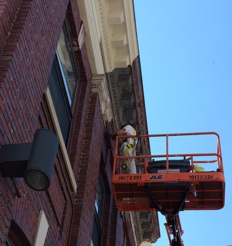 Deborah Bigelow up on the boom in 2017, completing her restoration of the cornice of the Telephone Building at 291 Main Street.  Photo Credit: Beacon Historical Society