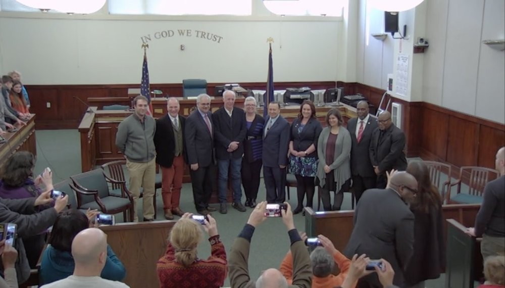 The local paparazzi (aka friends and families showing support).  Photo Credit: Screenshot of Swearing In Ceremony from video produced by Peter Skorewicz.