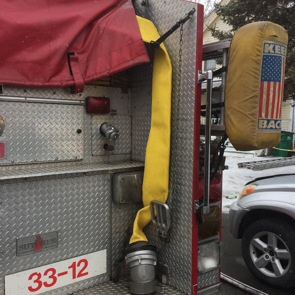 Pictured here is the yellow water hose that a vehicle drove over when it was full of water and in the street. The driver went around firemen, who had been blocking the street for safety. Photo Credit: Katie Hellmuth Martin