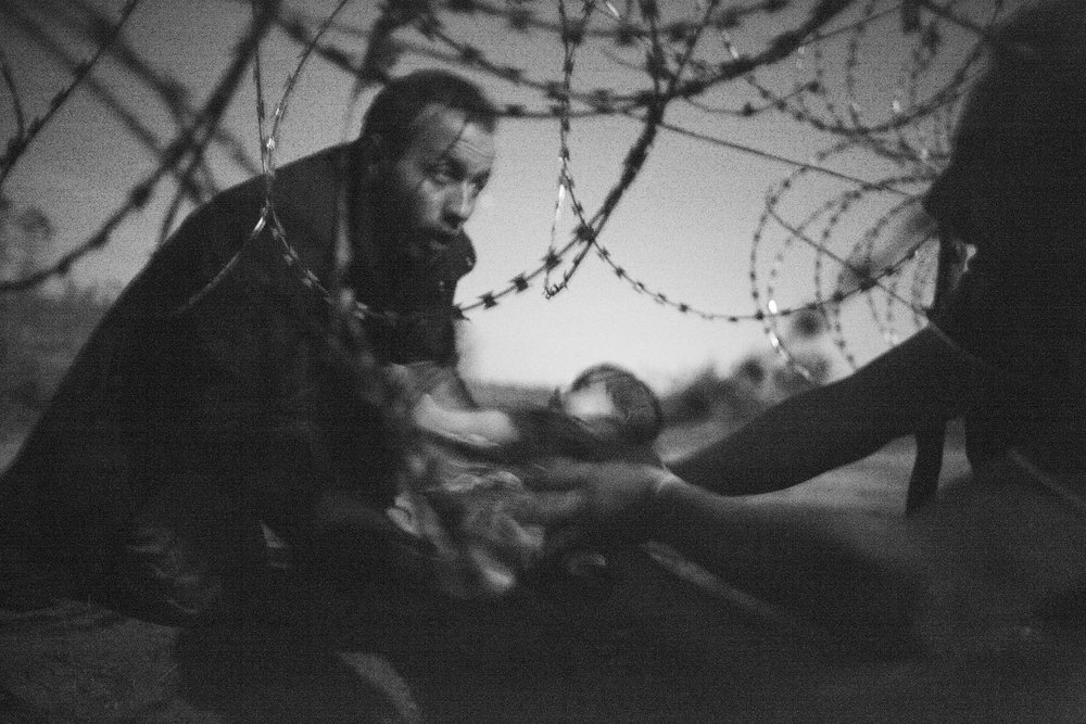 A man handing a child under a barbed wire fence from the village of Horgoš in Serbia to Röszke in Hungary during the European migration crisis in 2015. Photograph: Warren Richardson