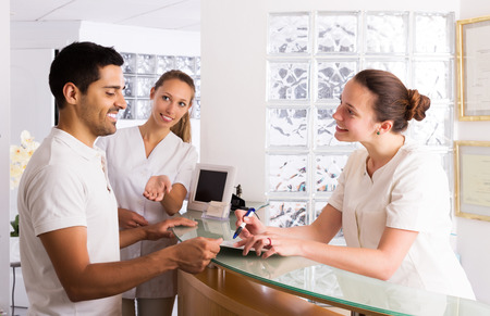 43822740_S_receptionist_check_in_appointment_man_woman_nurse_desk_office.jpg