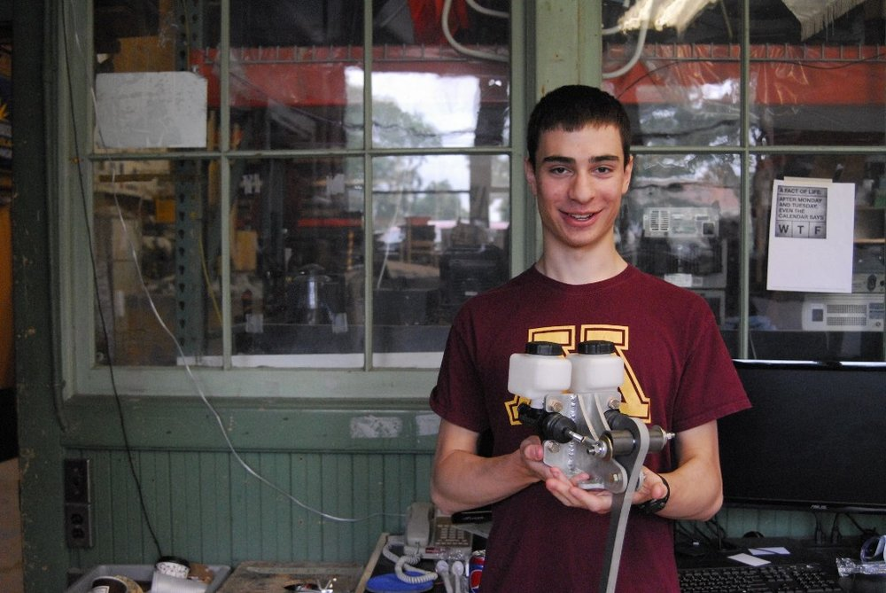 Matthew Balafas holds his completed master cylinder braking assembly.
