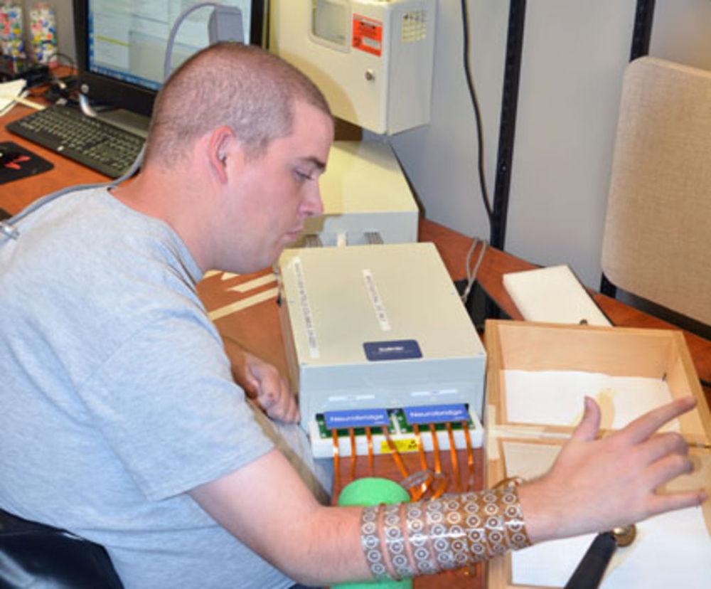 The quadriplegic Ian Burkhart picks up a spoon T.R. Massey