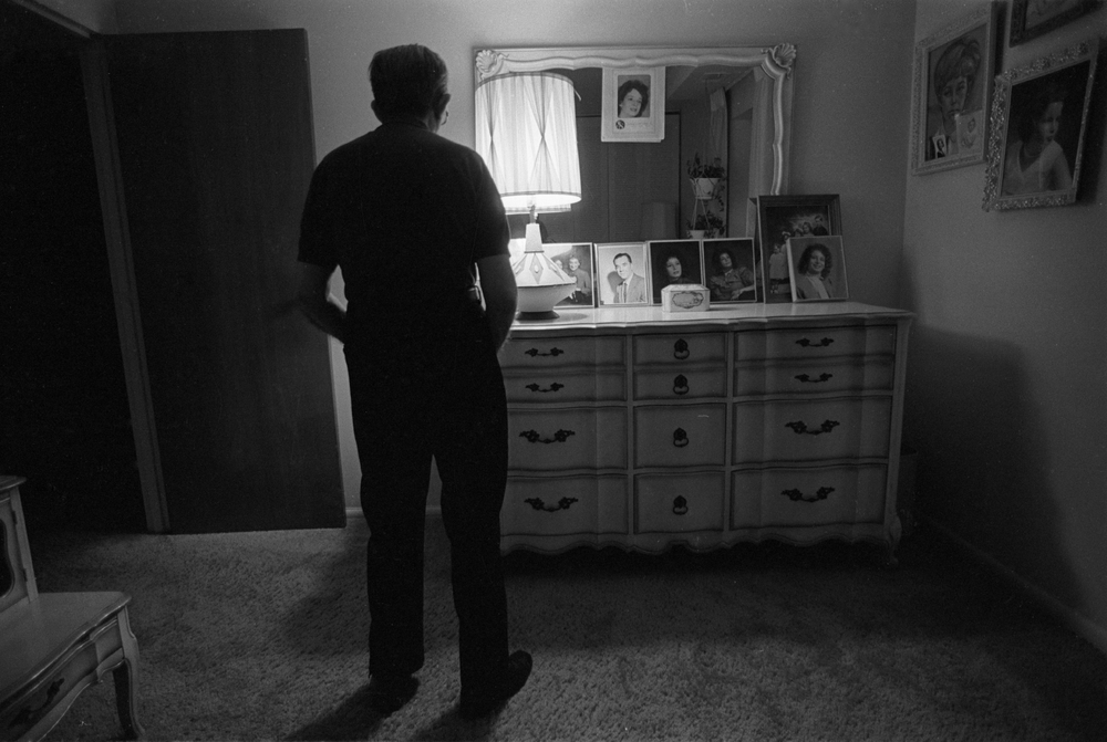 Max stands in the room where the family pictures are kept, confused by the photographs of himself, his wife, and other relatives.