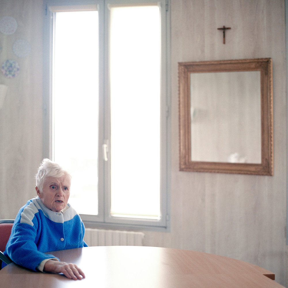 Resident sits in the Alzheimer's ward's common room. She is talking aloud to someone i can't see. The age-related disease is a mystery to the western world as very little is known about its causes. There is no cure for Alzheimer's disease although medication has been proven to slow down the developing process of the symptoms.