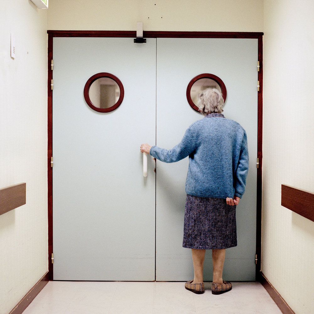 Resident stands in front of the ward's locked exit. Doors and blocked passing's are disturbing elements to a person suffering from Alzheimer's due to the common symptom to regularly often wander about. As a result of the potential risk of getting lost, the ward is confined for security reasons according to the « principle of precaution».