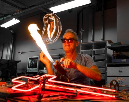 Le Boss - Gérald Collard est un artisan du verre spécialisé en fabrication du néon depuis plus de 30 ans. Reconnu à travers le monde entier, il a travaillé en collaboration avec de nombreux artistes et compagnies de renommée internationale sur des projets allant de campagnes publicitaires à pochettes d'album et d'installations artistiques à la conception de décors lumineux pour la scène ou les plateaux de tournage. Boss incontesté du néon artistique à Montréal, il dédie sa vie à garder vivant ce médium unique dont il est passionné depuis son plus jeune âge.