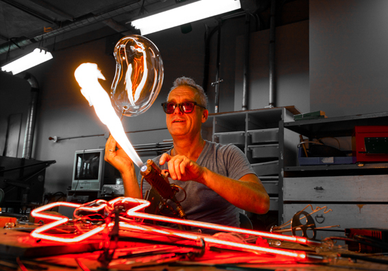 The Boss - Gérald Collard is a glass artist who has specialized in the fabrication of hand-blown neon signs for over 30 years. Recognized all over the world, he has worked in collaboration with many international artists and companies on projects ranging from advertising campaigns to album art, from artistic installations to light structures for stage or film sets. Undisputed boss of artistic neon in Montreal, he dedicates his life to the survival of this unique craft, which has fascinated him for as long as he can remember.