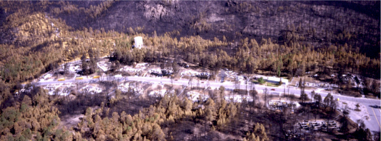 Several buildings destroyed during (not by) the 2000 Cerro Grande Fire near Los Alamos, New Mexico, illustrate an important fact. The fire spread via flames and firebrands. The unconsumed vegetation surrounding the building sites shows that it was not the trees that caused the buildings to burn, but the buildings that caused nearby trees (and nearby buildings) to burn . Source: Jack Cohen, USDA Forest Service.