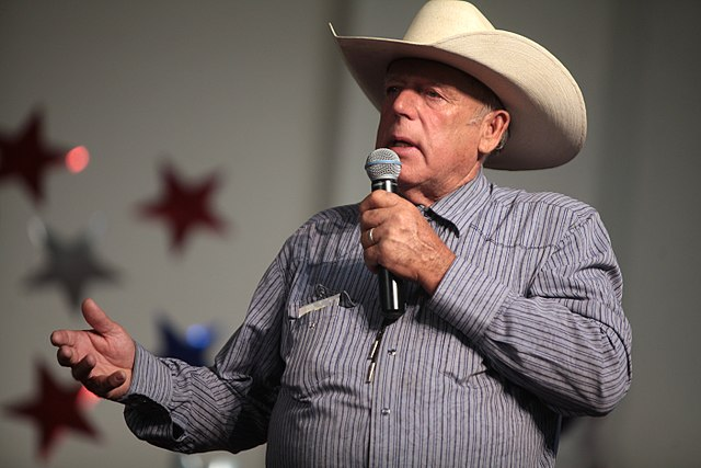 "Cliven Bundy spoke in 2014 at the American Academy for Constitutional Education at the Burke Basic School (""   A Mesa Arizona High Achieving Back to Basics Charter School   "" that uses the original 1836 versions of McGuffey's Readers to teach reading ) .  Source: Gage Skidmore via Wikipedia."